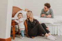 Pareja alegre mirando al niño por la cama - foto de stock