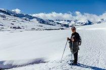 Людина позують з Трекінгові палиці в snowy луг — стокове фото
