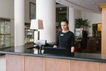 Pretty brunette hotel worker standing at reception — Stock Photo