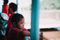 LAOS, LUANG PRABANG: Niño de pie en el barco y mirando hacia otro lado mientras navega en la naturaleza . - foto de stock