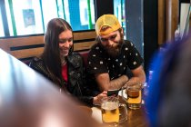 Cheerful girl browsing smartphone by smiling bearded man at restaurant — Stock Photo