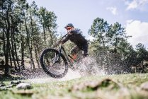 Велосипедист брызгает водой с горного велосипеда на лужайке под солнцем — стоковое фото