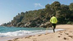 Вид сзади человека, бег трусцой вдоль идиллического пляжа — стоковое фото