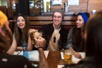 Amis heureux tinter les verres de bière à table au restaurant — Photo de stock