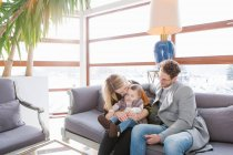 Cheerful family sitting on couch and kissing child — Stock Photo