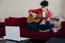 Junger Mann spielt zu Hause vor Laptop Gitarre — Stockfoto