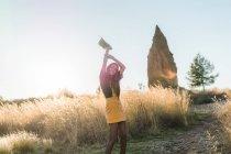 Жизнерадостная женщина, махнув рукой с шляпу на светлой природе — стоковое фото