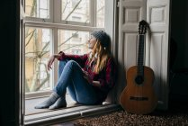 Smiling young woman sitting at window by guitar — Stock Photo