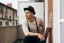 Мрійливий людина в марочні одягу, сидячи на балконі — стокове фото