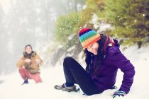 Happy friends playing snowballs in woods — Stock Photo