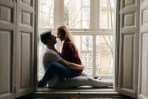 Cheerful couple sitting on window sill and embracing — Stock Photo