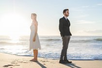 Bridal couple posing on sunny beach and looking in opposite side — Stock Photo