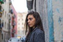 Молодая женщина брюнетка, опираясь на стене шероховатый — стоковое фото