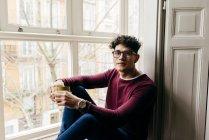 Человек с чашкой сидит на подоконнике и улыбается — стоковое фото