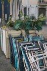 Pilha de cadeiras velhas de enferrujado em caixa de madeira com palma em vaso na rua da cidade. — Fotografia de Stock