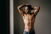 Hombre negro sin camisa posando con los brazos levantados en la ventana - foto de stock