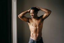 Hombre alegre sin camisa posando con los brazos levantados y mirando a la ventana en casa . - foto de stock