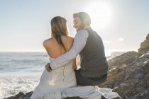 Sensual groom sitting with bride at coastal cliffs and looking at her — Stock Photo
