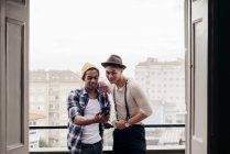 Amici multietnici in cerca di smartphone sul balcone — Foto stock