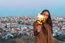 Cheerful young woman with sparkler against town at dusk — Stock Photo