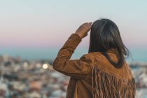 Rear view of brunette woman looking at city in dusk — Stock Photo