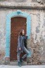 Giovane donna che si appoggia sulla porta grungy e rivolto verso l'obiettivo — Foto stock