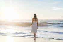 Vista posteriore della ragazza tenera in abito da sposa in riva mare panoramico — Foto stock