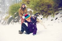 Cheerful friends playing snowballs with dog in woods — Stock Photo