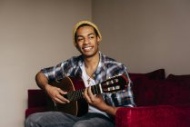 Cheerful man playing guitar on sofa at home — Stock Photo