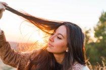 Веселая женщина играет с волосами в природе — стоковое фото