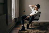 Стильный мужчина в винтажной одежде позирует на стуле у окна — стоковое фото