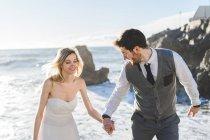 Веселая супружеская пара, бегущая волнами по берегу — стоковое фото
