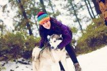 Смеющаяся женщина играет с собакой на снегу и смотрит в камеру — стоковое фото
