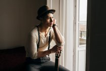 Вдумчивый молодой музыкант с гитарой сидел у окна и глядя. — стоковое фото