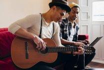 Junger Mann spielt Gitarre, während Freund Laptop auf Sofa zu Hause benutzt. — Stockfoto