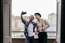 Jovens amigos multiétnicos de pé juntos e tomando selfie na varanda em casa . — Fotografia de Stock