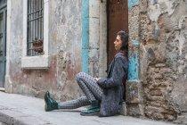 Jeune femme penchée sur le pas de la porte grungy à la rue — Photo de stock