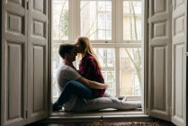 Side view of young couple kissing on window sill at home — Stock Photo