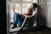 Lächelnde paar auf der Fensterbank zu Hause glücklich umarmt — Stockfoto