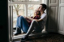 Smiling couple hugging happily on window sill at home — Stock Photo