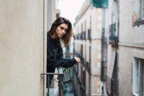 Красива жінка, спираючись на поручня у вікні програми і, дивлячись на камеру. — стокове фото