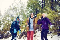 Happy friends throwing snowballs at camera in woods — Stock Photo