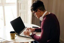 Young man sitting at table and typing on laptop at home. — Stock Photo