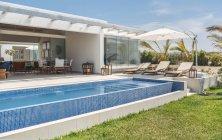 Grande piscina blu e comodi lettini sotto l'ombrellone in villa nella giornata di sole . — Foto stock