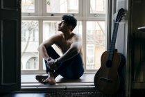 Pensiero uomo senza camicia seduto sul davanzale della finestra con le gambe incrociate — Foto stock