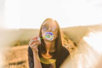 Young woman in sunglasses blowing soap bubble in nature om  sunny day. — Stock Photo