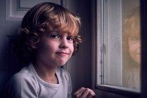 Garçon adorable, posant à la fenêtre et regarder la caméra — Photo de stock
