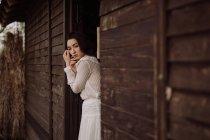 Junge zarte Brünette in weißem Kleid lehnt an Holztür und schaut weg. — Stockfoto