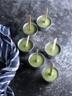 From above of metal tray with cups filled with green fruit ice pops on table. — Stock Photo