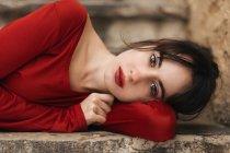 Brunette en robe rouge couchée sur une marche en pierre et regardant la caméra . — Photo de stock